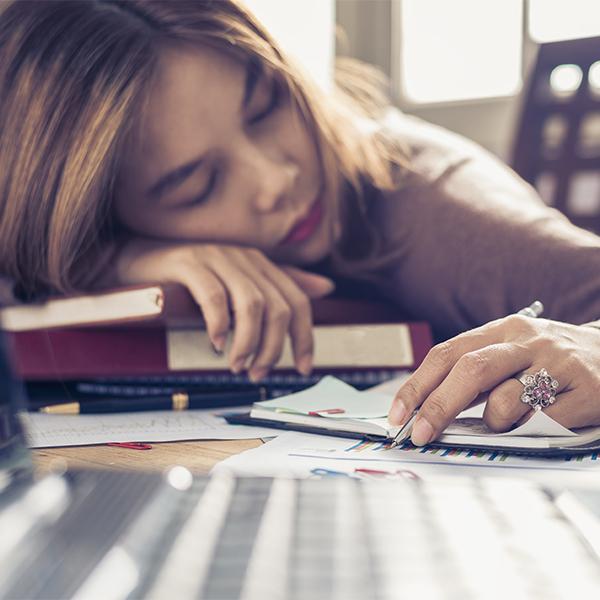 women sleeping on desk with pen