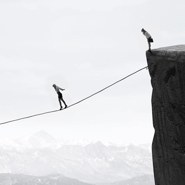 women standing on cliff tightrope
