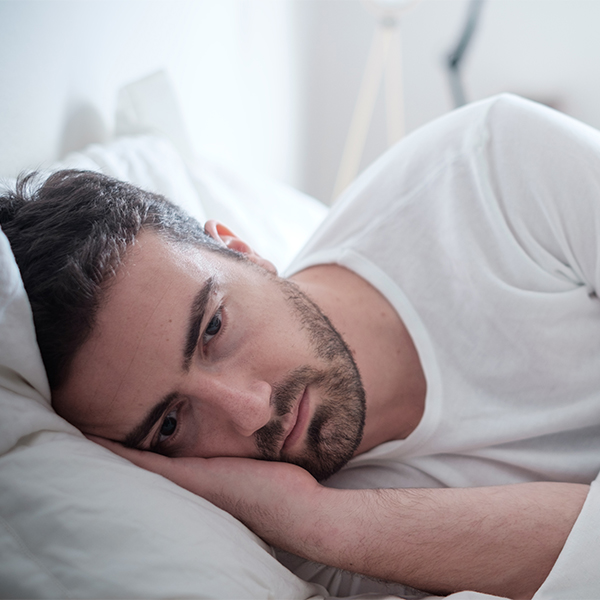 man laying in bed eyes open